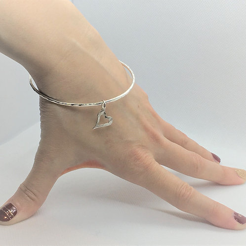 Solid Petite 925 Sterling Silver Bangle Lightly Hammered with a Hammered Heart Charm. Side View.