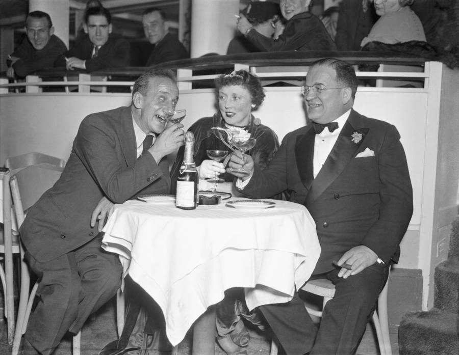 Jimmy Durante, abundant-nosed comedian, explains New York night life to Mayor and Mrs. George J. Zimmerman of Buffalo, N.Y., at the Cotton Club, 1936.