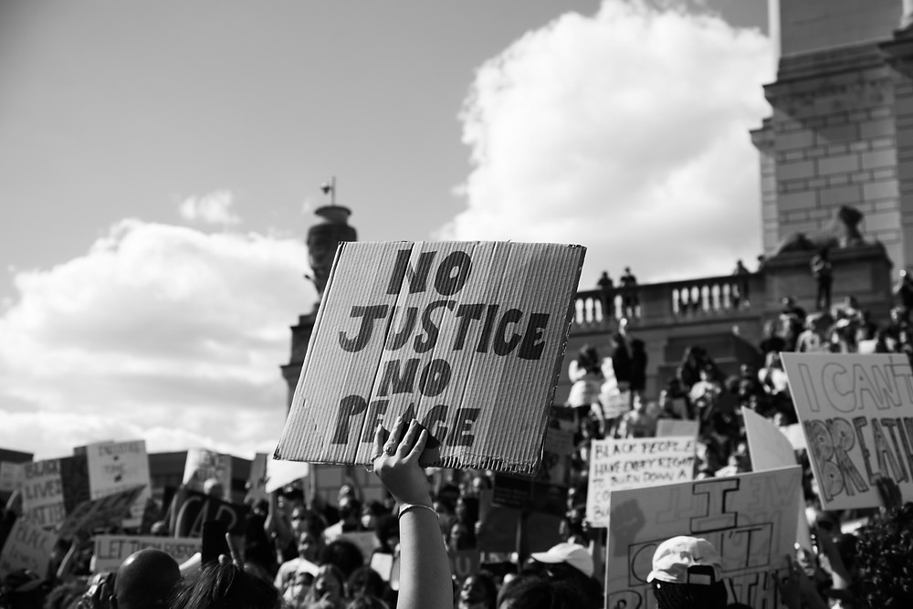 Protestors holding up sign that says No Justice No Peace