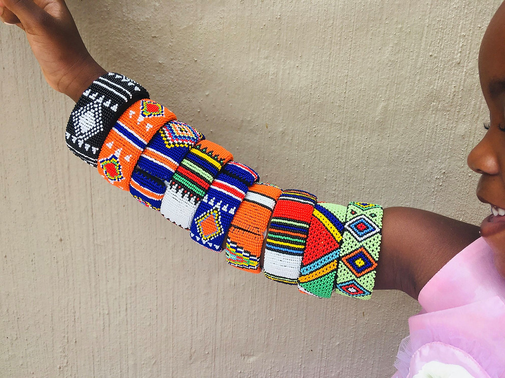 Colourful african bangles on the arm of a child