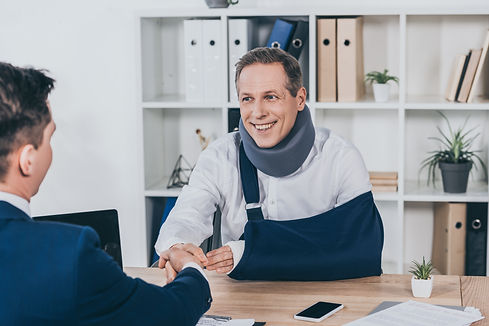 worker in neck brace with brokenarm and businessman in blue jacket shaking hands over tabl
