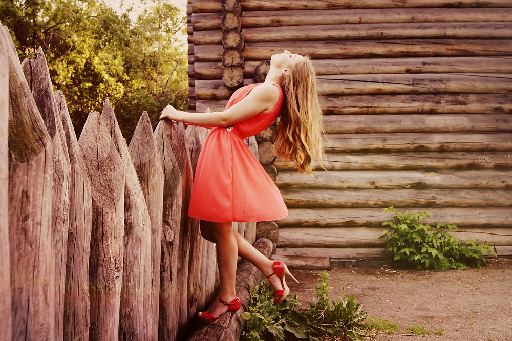 beautiful blond in dress standing at fence