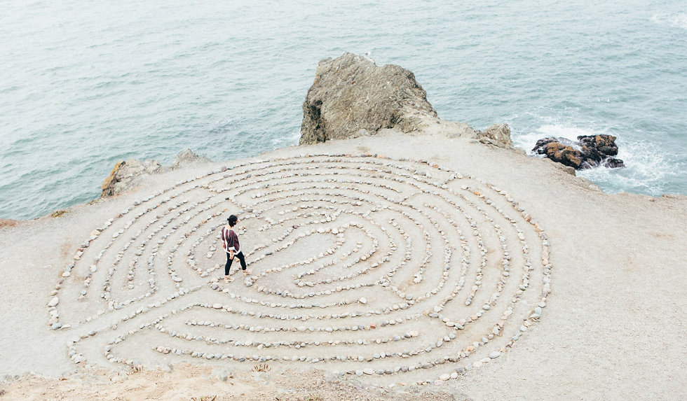 Woman walking a labrynth along a seaside