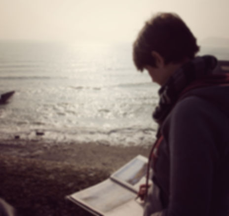 photo of Amanda Hoskin inting in her sketchbook on  a beach