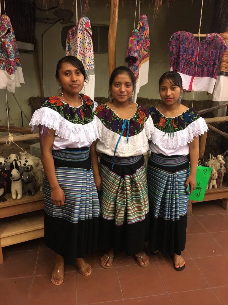 Mujeres vestidas con trajes de tejidos Huipil.
