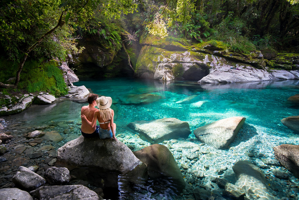 couple at hidden blue pool in milford sound