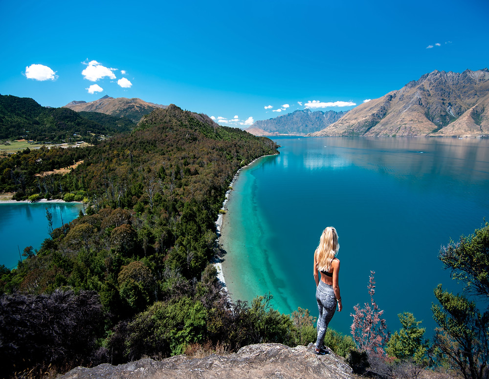 girl standing at bobs cove overlooking lake wakatipu
