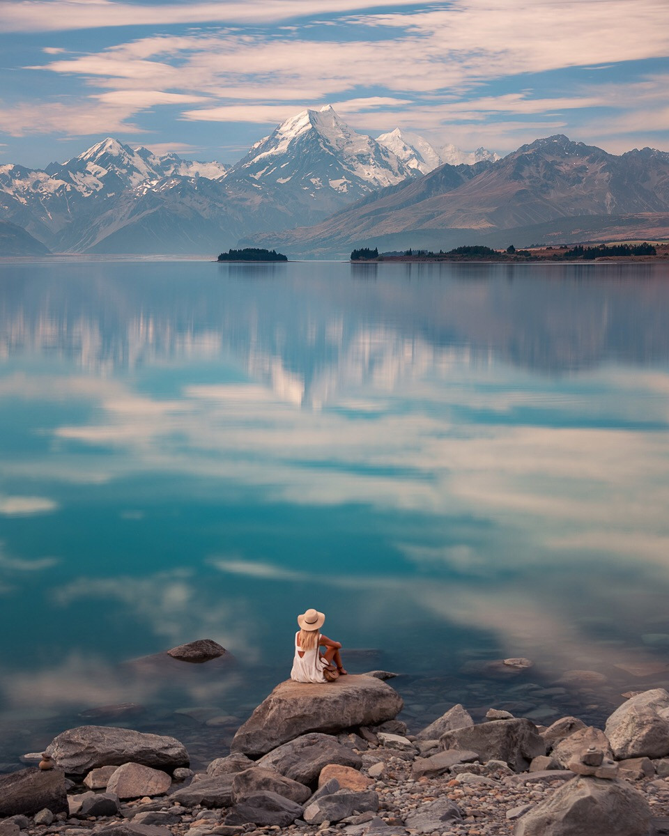 Charlotte Maddock sitting on a rock overlooking Mt Cook over Lake pukaki