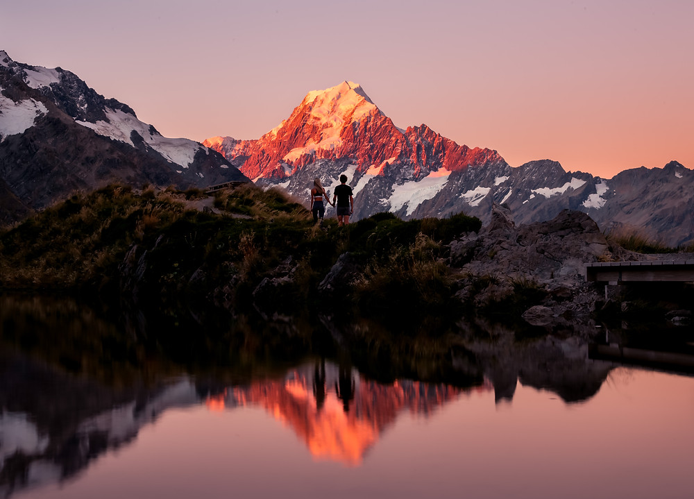 couple with mt cook at sunset reflected in sealy tarns