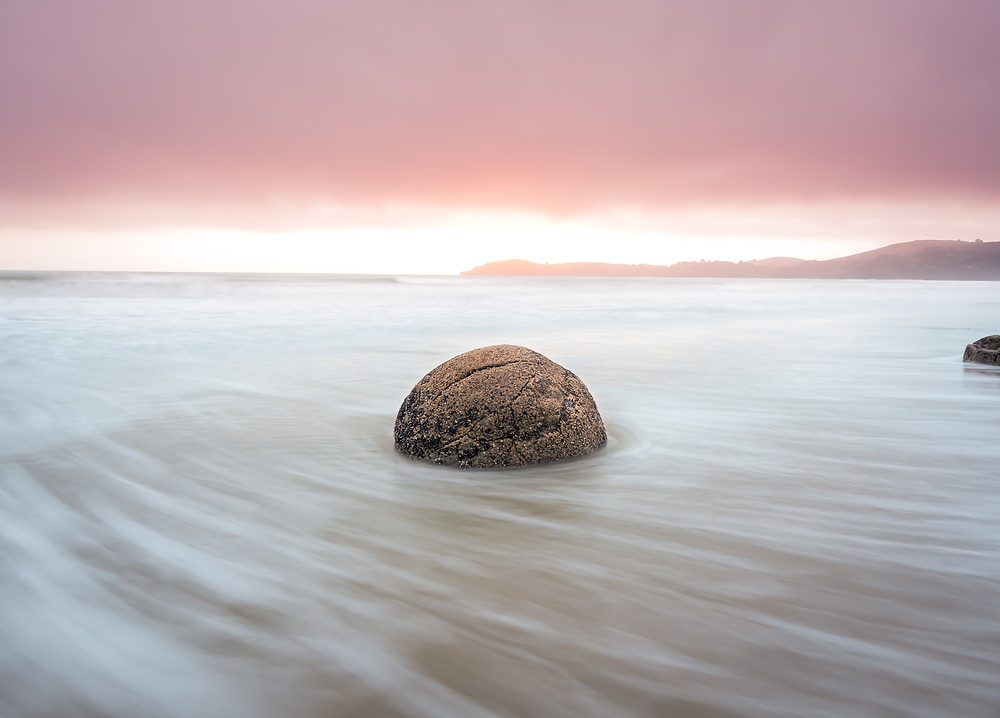 single moeraki boulder with water swirling around sunrise