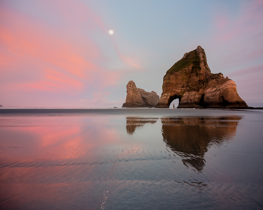 full moon set at sunrise wth couple at whaririki beach