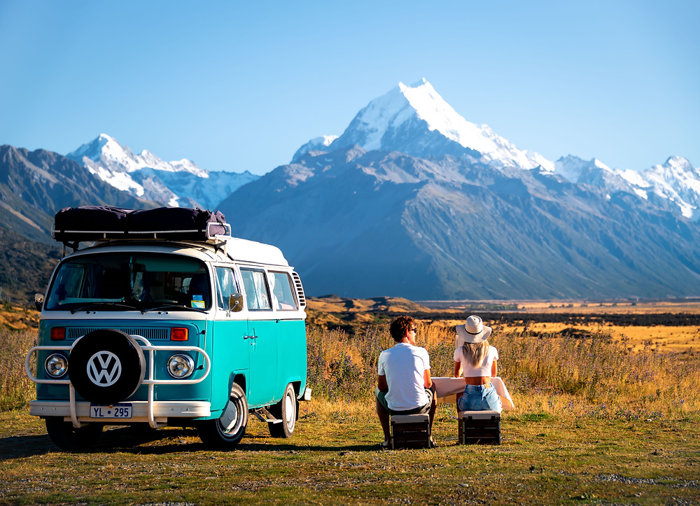 man and woman sitting down with kombi van with mt cook in background