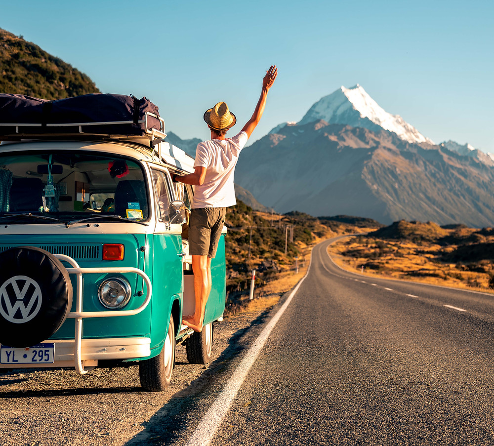 man leaning out of kombi van on side of road with mt cook