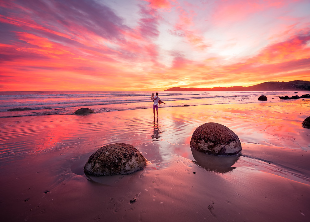 couple at moeraki boulders for explosive sunrise