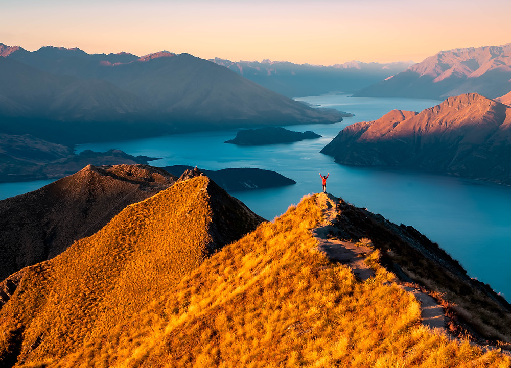 man standing on edge at roys peak at sunset