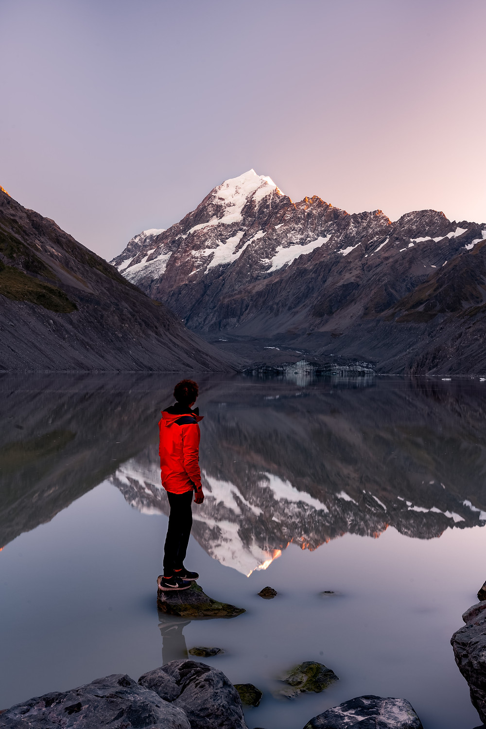 man on rock at hooker lake with sunrise on mt cook