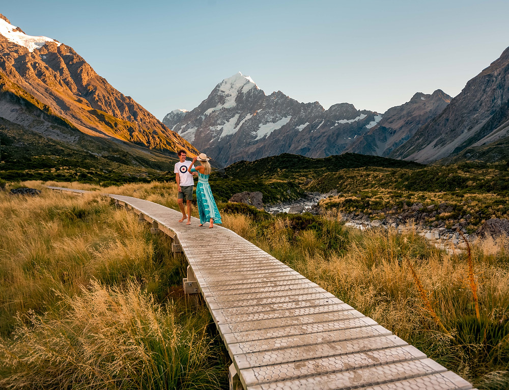couple on boardwalk on hooker valley track overlooking mt cook