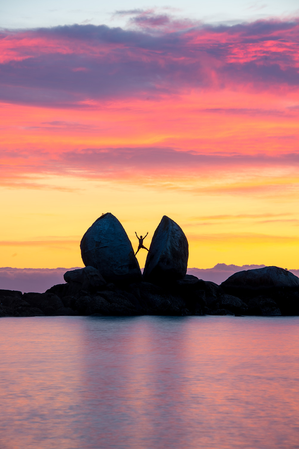 man silhouette at split apple rock at sunrise