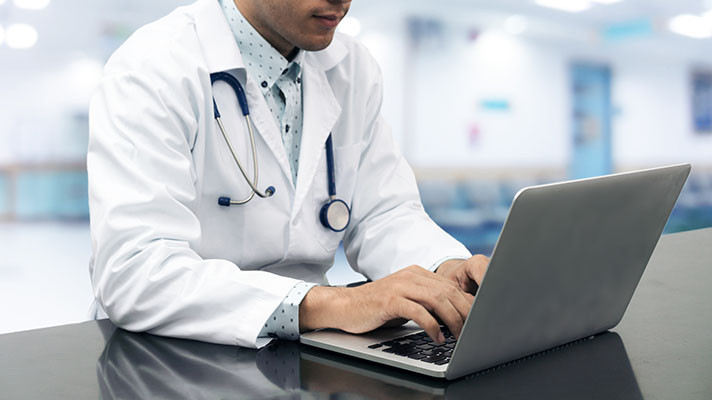 Medical professional entering notes into computer