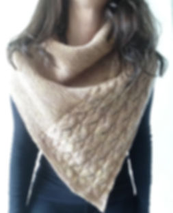 close up of brown haired latina girl wearing hand-knitted faux-cabled brown shawl on a white background