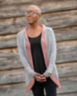 black woman wears hand-knitted grey cardigan with colorful collarband on a wood background