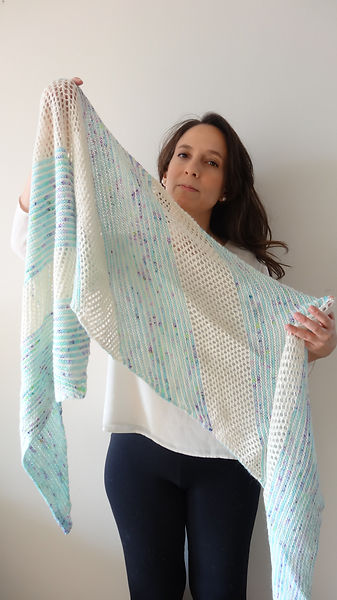 girl holding knitted shawl in acqua and off-white yarns, worked in a combination of garter stitch and mesh