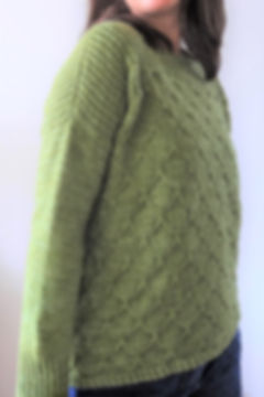 brown haired latina girl with arms extended on the sides wears hand-knitted green sweater on a white background