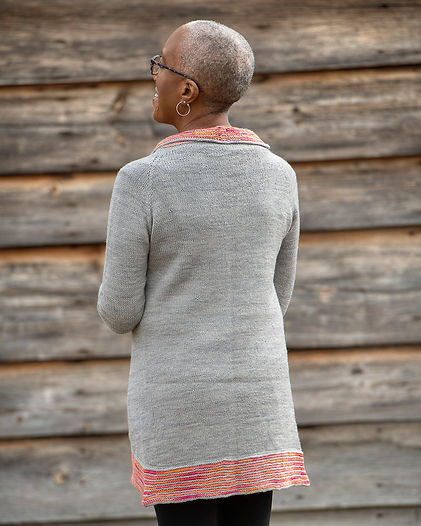 black woman shows the back of a hand-knitted grey cardigan with colorful collarband on a wood background