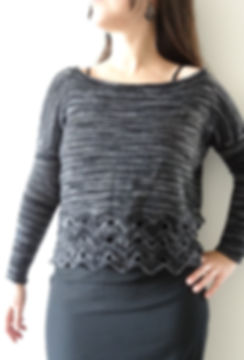 brown haired latina girl with left hand on hip wears hand-knitted black sweater with lace detail on hem on a white background