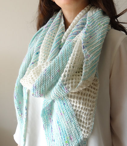 close up of hand knitted shawl in acqua and off-white yarns, worked in a combination of garter stitch and mesh
