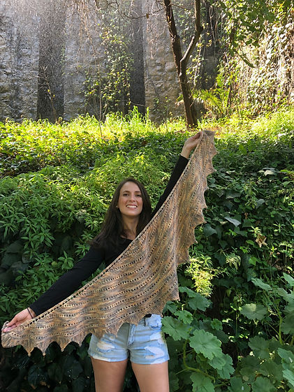 brown haired latina girl holds up hand-knitted brown shawl on a leaf and stones background