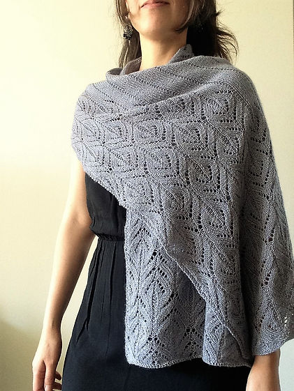 close up of hand-knitted grey lace wrap worn by brown haired latina girl on white background