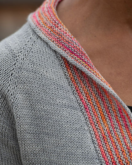 close-up of black woman wearing hand-knitted grey cardigan with colorful collarband
