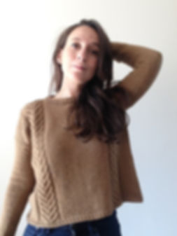 brown haired latina girl with left arm raised behind head wears hand-knitted brown cable sweater with jeans trousers on a white background