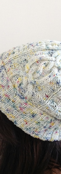 brown haired girl facing away from the camera wears hand-knitted speckled white blue yellow and red cabled bearnie