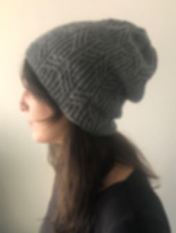 brown haired girl facing away from the camera wears hand-knitted grey cabled bearnie