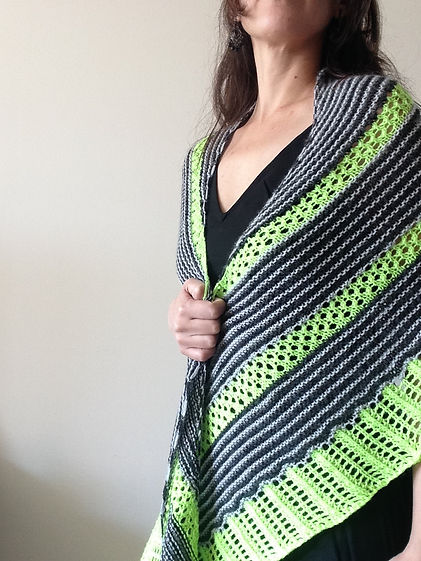 brown haired latina girl wears hand-knitted green, black and grey striped crescent shawl on a white background