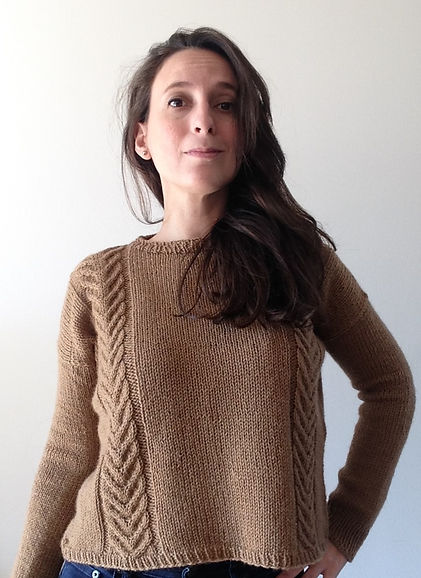 brown haired latina girl with left hand on hip wears hand-knitted brown cable sweater with jeans trousers on a white background