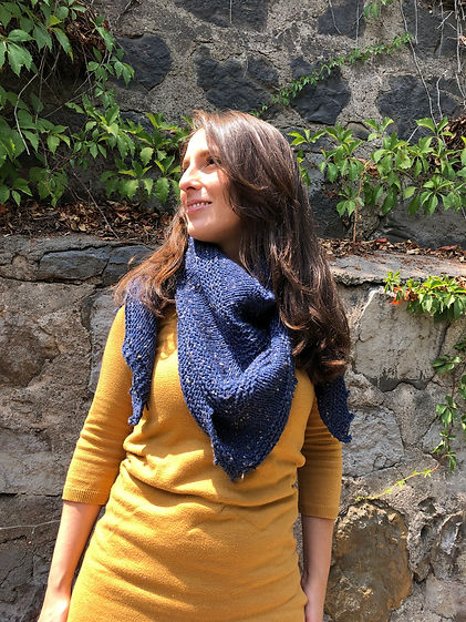 close up of brown haired latina girl wearing hand-knitted blue triangular shawl, yellow dress and black leggings on a stone background