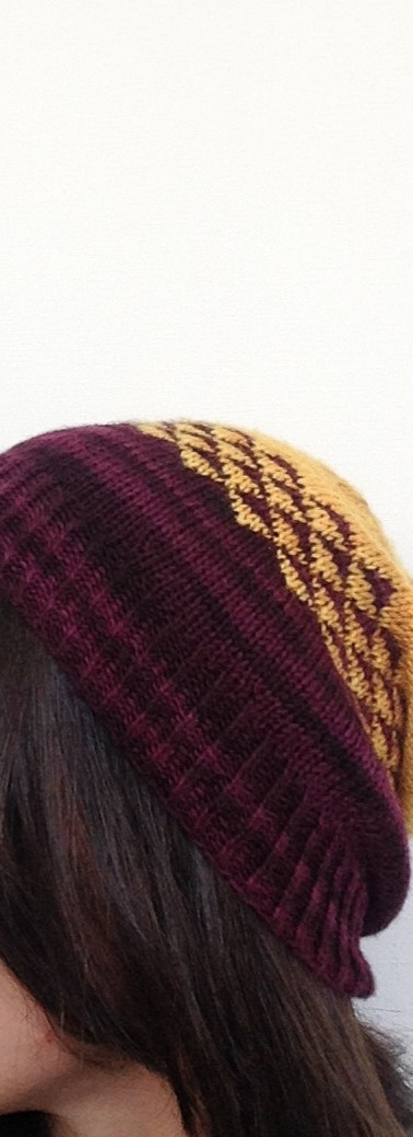brown haired latina girl wears hand-knitted yellow  and purple fair-isle beanie on white background