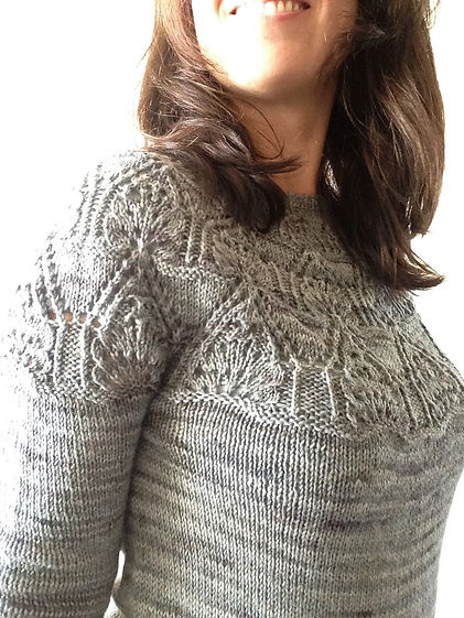 close-up of brown haired latina girl wears hand-knitted sweater with lace round yoke and french sleeves on a white background