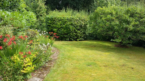 Floral borders, mossy old stone paving and lawn