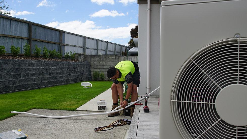 An ATL technician installing a heat pump