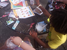 Two children do PBS Kids project outdoors