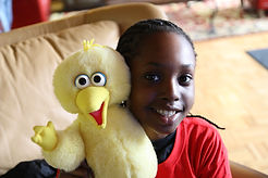 Young girl holds Big Bird stuffed animal and smiles at the camera