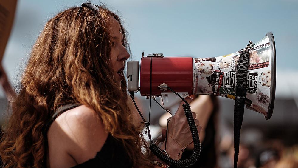 woman holding megaphone speaks