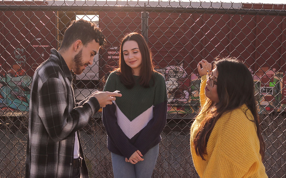 Two women and a man stand in front of a fence and talk.