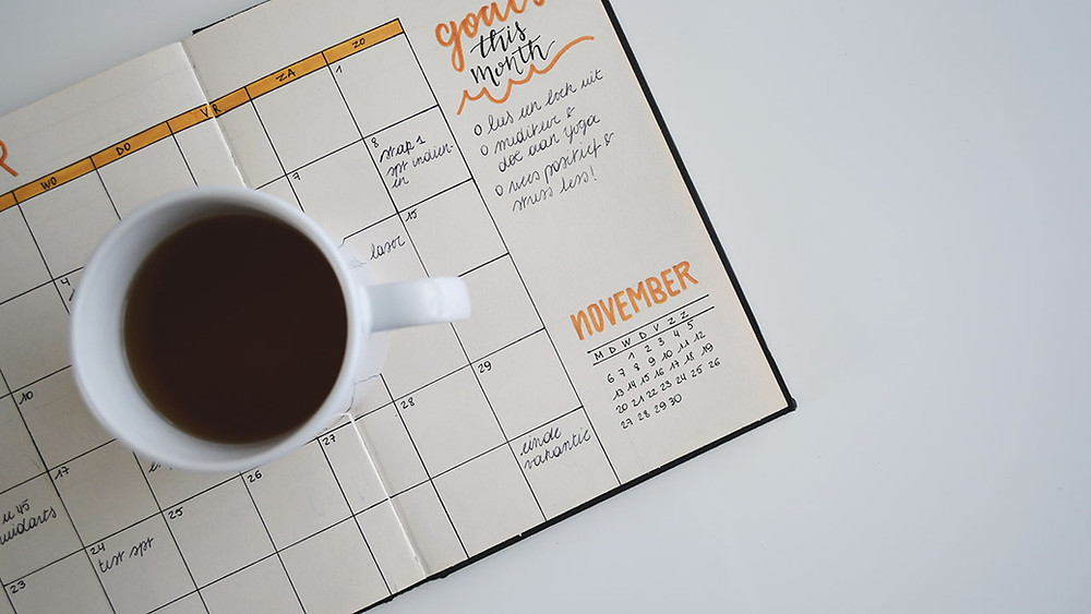 coffee cup on top of calendar