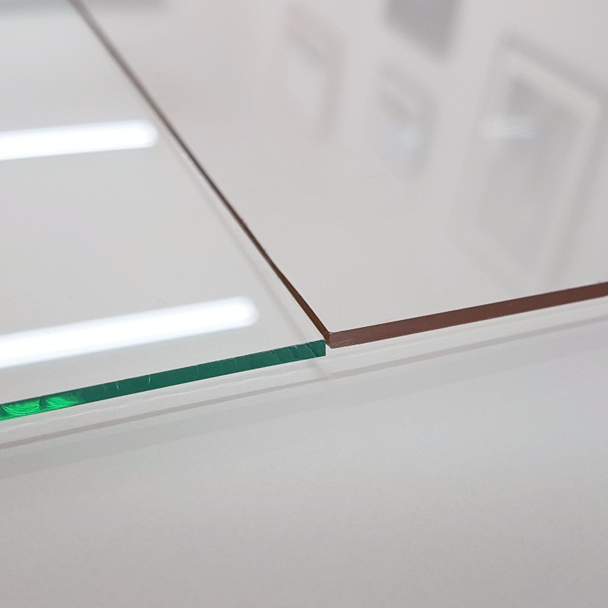Regular glass (left) has a green tint which can affect the colours of the artwork behind it. Conservation glass (right) offers a more neutral tone.
