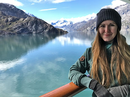 A picture of Ashley Ingiosi leaning on railing with Glacier Bay, Alaska in the background.